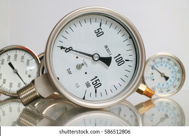 Row of metal steel high pressure gauge meters or manometers with brass fittings on tubing pipeline at LNG or LPG natural gas distribution station  or factory facility isolated on white background.