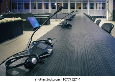 A row of microphone and headphone sets for speech and translation on a business or congress meeting on a desk. Translation booths are seen in the background.