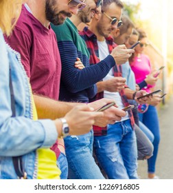 Row of millennials young friends look at the mobile smart phone. Sunlight effect. Concept of youth, tech, social and friendship