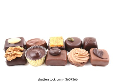 row of mixed chocolates isolated on white