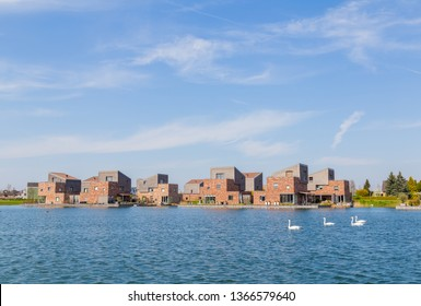 Row of modern brick houses along water with white swans in a family friendly suburban neighborhood in Houten in the Netherlands.