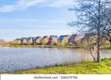 Row of modern brick houses along water in a family friendly suburban neighborhood in Veenendaal in the Netherlands.