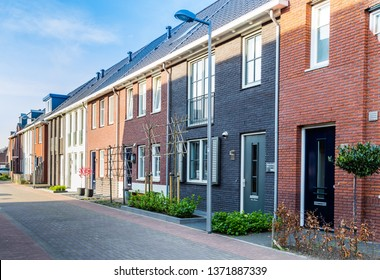 Row of modern brick houses in a family friendly suburban neighborhood in Veenendaal in the Netherlands.