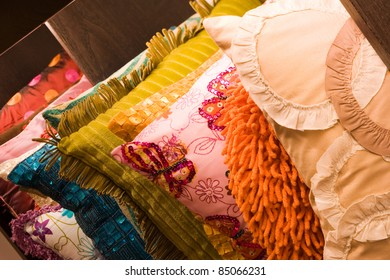 row of modern colorful cushions on a shelf. different shapes and fabrics