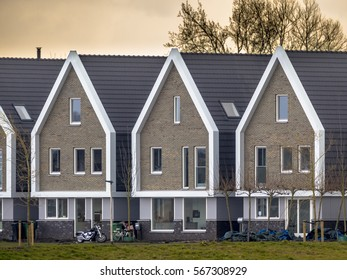 Row of modern identical free standing houses in the Netherlands at sunset