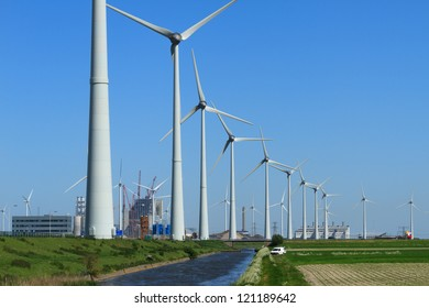 Row of modern wind turbines and a power plant being constructed in the Eemshaven, Holland.