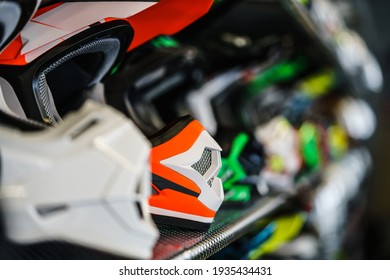 A row of motorcycle helmets on the shelf in the store.