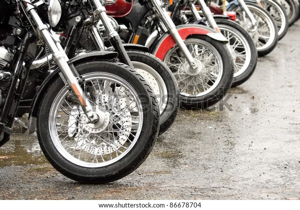 row of motorcycles parked together on a rainy day