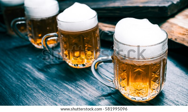 Row of mugs of beer or ale on rustic black wood. Closeup wide view