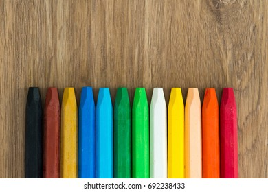 Row of multi colored wax crayons on the wooden board