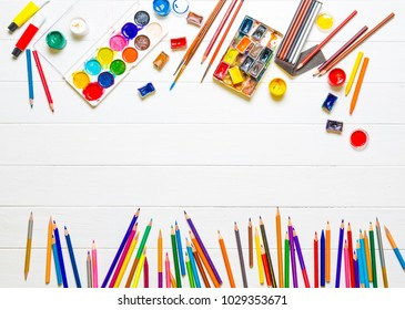 Row of multicolored pencils and watercolors with brushes on white wooden background, copyspace, top view. Still life of various drawing tools