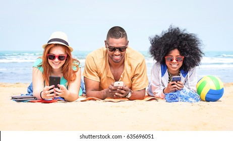 Row of multicultural friends using phone lying on beach - Happy african and american students texting messages are looking addicted at mobile technology and social media post - Modified ball and watch