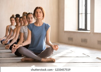 Row multi-ethnic beautiful girls sitting in lotus position meditate during yoga session in the morning at sports studio, diminishing perspective. Enlightenment, unity of spirit mind and body concept