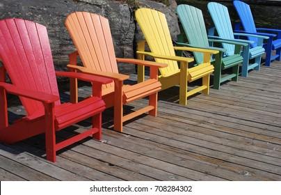 Row Of Muskoka Adirondack Chairs On The Dock In The Summer Sunshine
