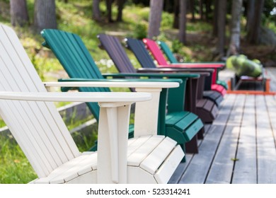 a row of Muskoka chairs sitting on the dock facing out to the lake, inviting you to come sit for a while
