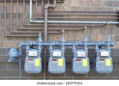 A row of natural gas meters and pipes against a two-toned brick wall
