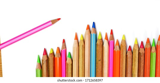 A row of neon pens lies on a sheet - a person paints with these pens on a white sheet - coloured pens as background