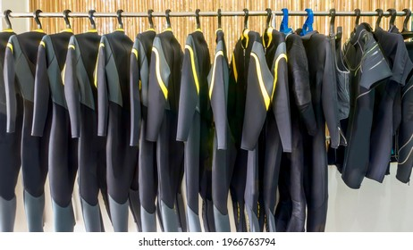 A row of neoprene diving wetsuits hanging on a rack in a resort dive shop in the Philippines.