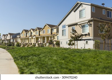 A row of new apartments with a lush grassy lawn in the foreground