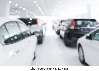 A row of new cars parked at a car dealership stock blurry