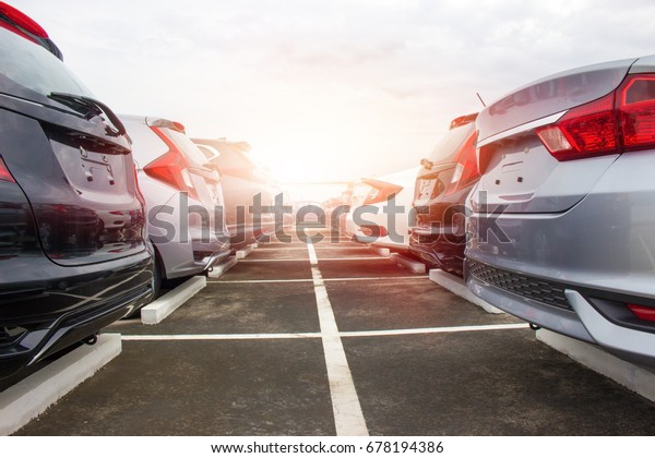A row of new cars parked at a car dealership stock
