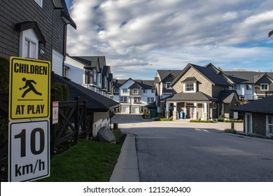 Row of new residential townhouses on a street. Family townhouses with concrete driveways and asphalt road in front.