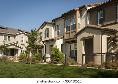 A row of new townhomes with a lush grassy lawn in the foreground.