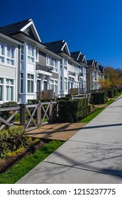 Row of new townhomes in a sidewalk neighborhood. On a sunny day in spring against bright blue sky.
