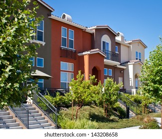 A row of new townhomes with yellow, gray, and dark red exteriors in San Jose, California.