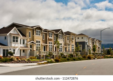 A row of new townhouses / condominiums along a city street.