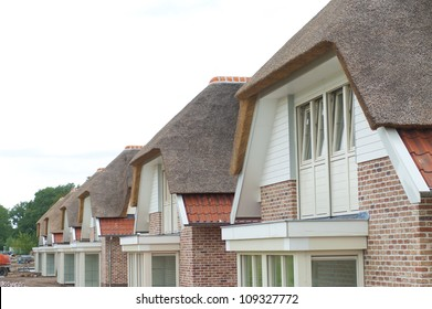row of newly build homes with thatched roofs