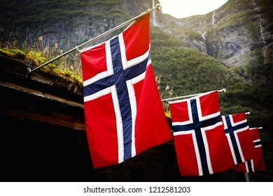 Row of norwegian flags outdoor on green nature, mountains in the background