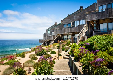 A row of oceanfront townhomes adjacent to a landscaped sand dune along the California coast.
