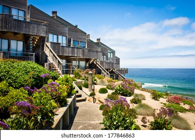 A row of oceanfront townhomes adjacent to a landscaped sand dune.