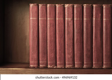 A row of old, battered, matching encyclopaedias (circa 1950s) lined up on a shelf, with titles removed to leave blank spines.  Red leather effect with gold striped trims.  Vintage effects applied.