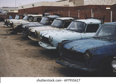 Row of old, blue trucks at a salvage yard in Mauritania.
