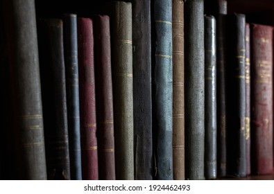 row of old books in the dark, without title