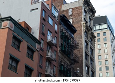 Row of Old Brick Apartment Buildings in Greenwich Village of New York City with Fire Escapes