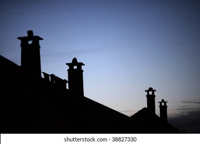 Row of old brick chimneys with moody bluish evening sky in the background