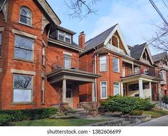 row of old brick detached houses with gables and large porches