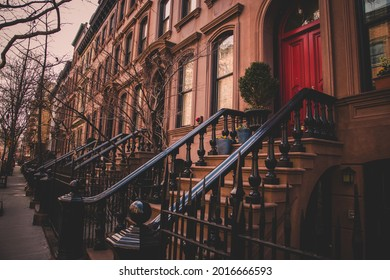 Row of old brownstone buildings along an empty sidewalk block in the Greenwich Village neighborhood of Manhattan, New York City NYC