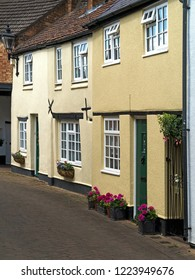 A row of old, cream painted cottages in Dean's Street Oakham, Rutland, UK