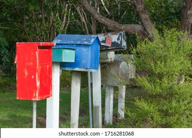 Row of old different style and color letter boxes amongst trees.