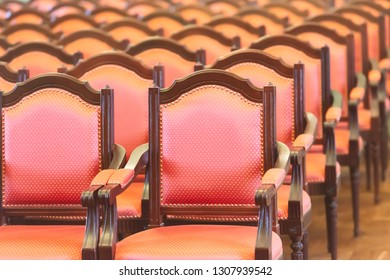 Row of old elegant red wooden chairs. Conference room or auditorium.