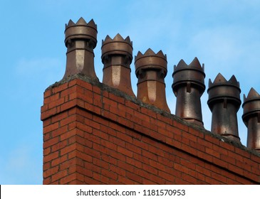 A row of old fashioned traditional clay chimney pots on a red brick support against a blue sky from when houses where built coal burning heating