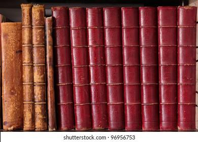 Row of old leather hardbound books on a shelf