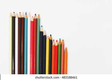 Row of old rustic used colored wooden pencils isolated on white background designer art work place supplies Top view close up