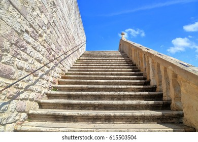 Row of old stairs ascending under the blue sky at the Basilica of San Francesco in Assisi, Umbria, Italy