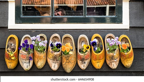 Row of old traditional handmade Dutch wooden clogs with blooming flowers in Zaanse Schans village near Amsterdam, Netherlands.