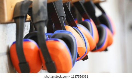 row of orange ear muffs ear protection on a rack. workplace health and safety deafness concept. safe work practice.
